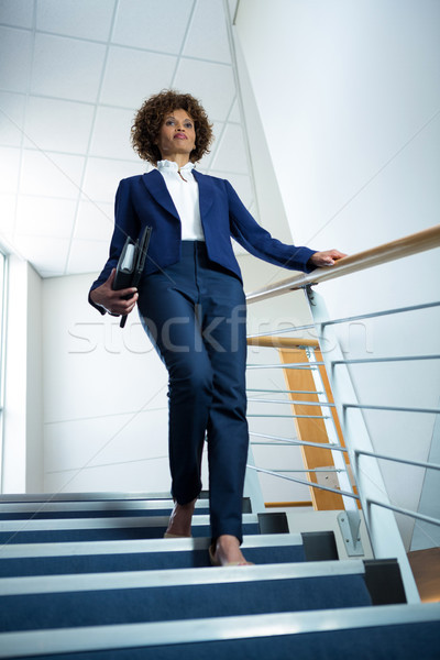 Businesswoman with diary climbing down the stairs Stock photo © wavebreak_media