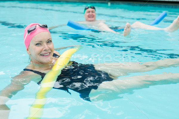 Mature couple swimming with pool noodles Stock photo © wavebreak_media