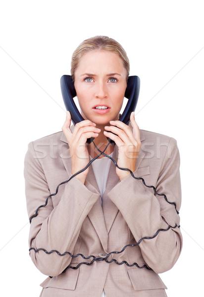 Stressed businesswoman trangled up in telephone wires Stock photo © wavebreak_media