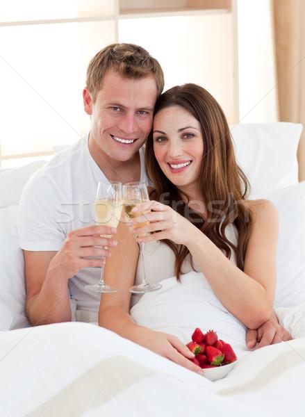 влюбленный пару питьевой шампанского клубники кровать Сток-фото © wavebreak_media