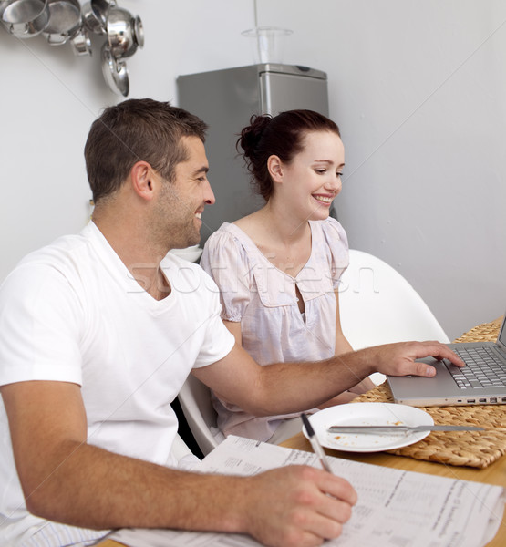 Couple working with a laptop in kitchen Stock photo © wavebreak_media