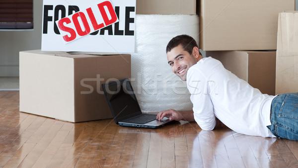 Atraente homem piso usando laptop casa feliz Foto stock © wavebreak_media