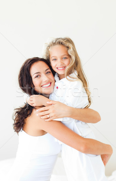 Delighted mother and daughter on a white bed against white background Stock photo © wavebreak_media