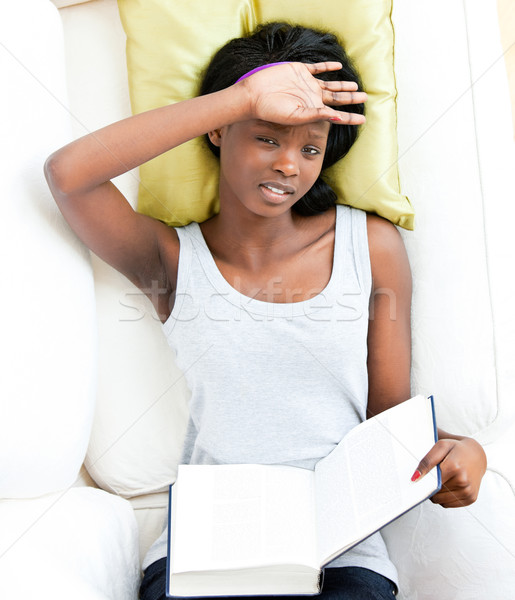 Afro-american teenager feeling sick holding a book lying on a sofa Stock photo © wavebreak_media