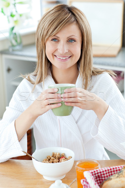 Beautiful woman holding a cup of coffee eating cereals in the kitchen Stock photo © wavebreak_media