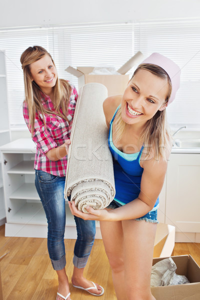 Enthusiastic women holding a carpet standing in the kitchen after moving Stock photo © wavebreak_media
