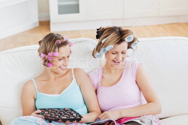 Close female friends with hair rollers eating chocolate reading a magazine at home on a sofa Stock photo © wavebreak_media