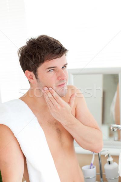 Moço loção após barba banheiro olhando câmera casa Foto stock © wavebreak_media