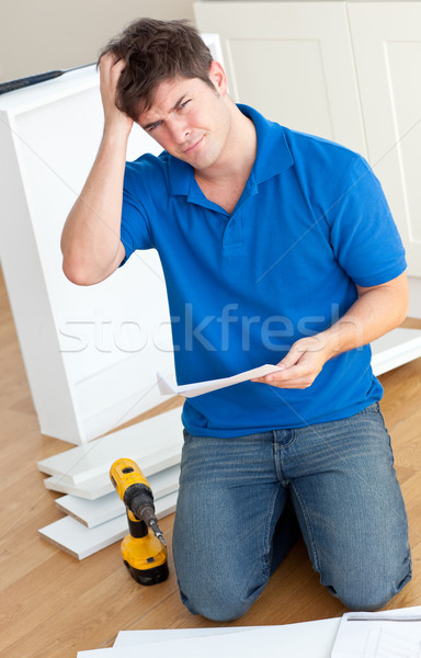 Incomprehensive caucasian man reading the instructions to assemble furniture in the kitchen at home Stock photo © wavebreak_media