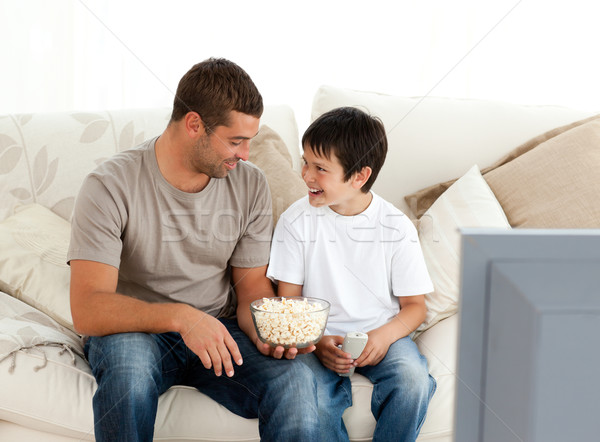Father and son watching television while eating pop corn on the sofa at home Stock photo © wavebreak_media