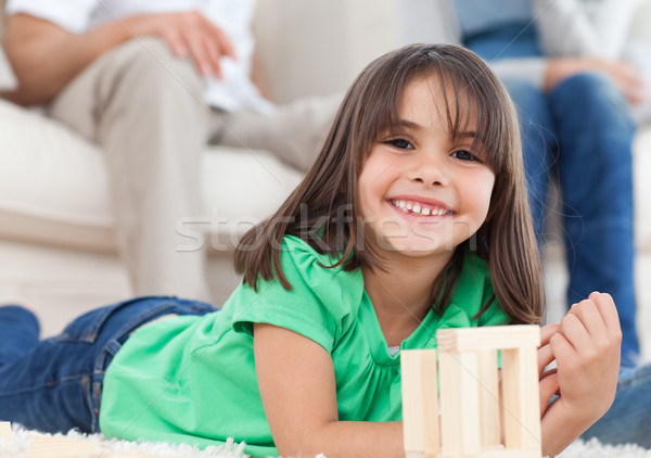 Cute little girl playing with dominoes in the living room with her parents Stock photo © wavebreak_media