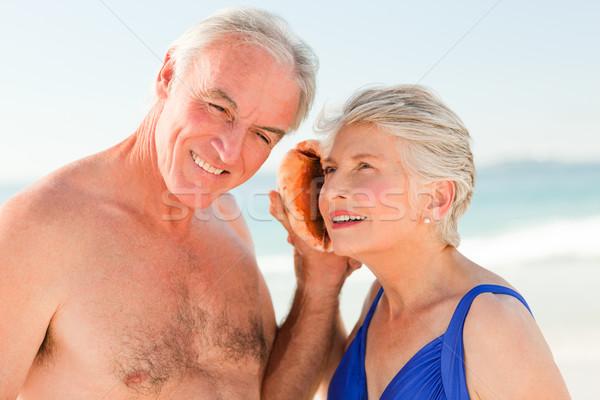 Retraite couple écouter shell plage sourire Photo stock © wavebreak_media
