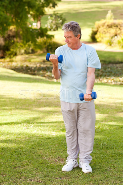 Stock photo: Elderly man doing his exercises in the park