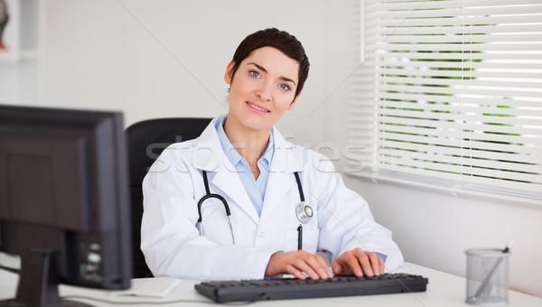 Sonriendo médico escribiendo ordenador oficina negocios Foto stock © wavebreak_media