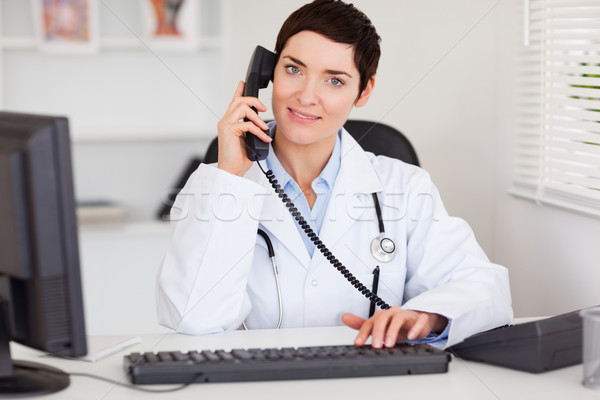 Smiling female doctor making a phone call in her office Stock photo © wavebreak_media