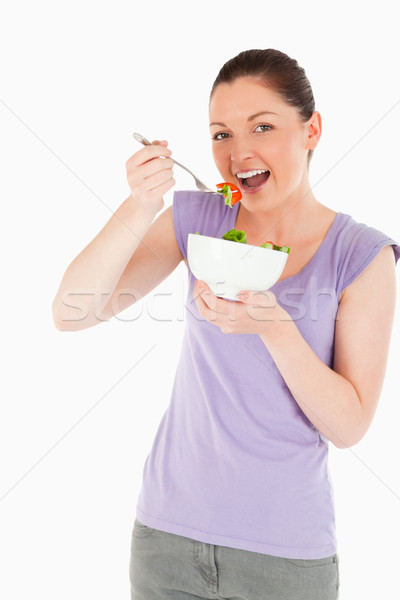 Stock photo: Good looking woman eating a bowl of salad while standing against a white background