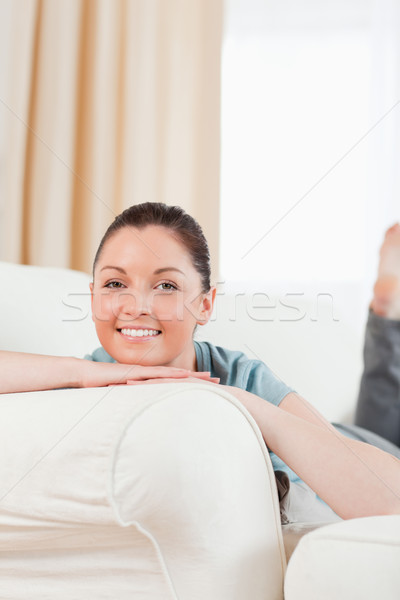 Stock photo: Lovely woman posing while lying on a sofa in the living room