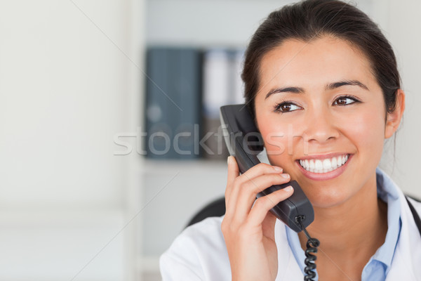 Stock photo: Good looking female doctor on the phone and posing in her office