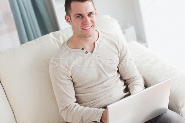 Stok fotoğraf: Gülen · adam · dizüstü · bilgisayar · kullanıyorsanız · oturma · kanepe · oturma · odası