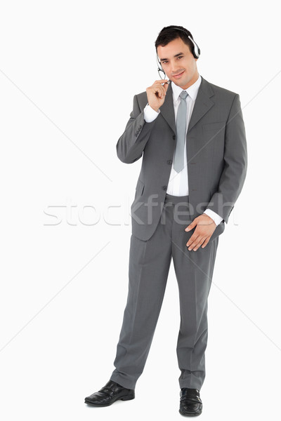 Young businessman with headset on against a white background Stock photo © wavebreak_media