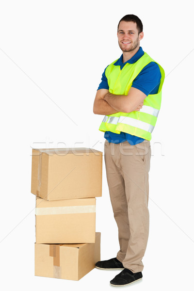 Smiling young delivery man with arms folded against a white background Stock photo © wavebreak_media