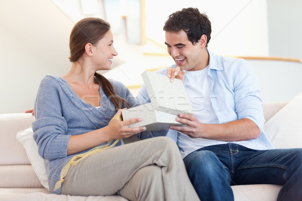 Man surprising his wife with a present in their living room Stock photo © wavebreak_media