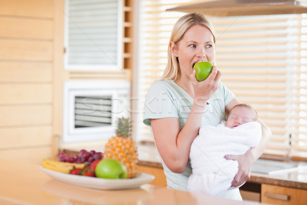 Young woman biting into apple with baby on her arms Stock photo © wavebreak_media