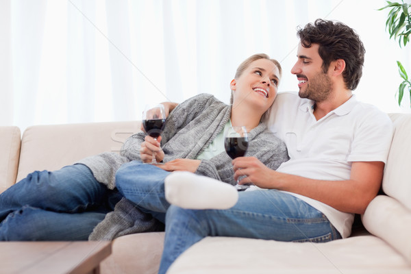 Young couple having a glass of red wine in their living room Stock photo © wavebreak_media