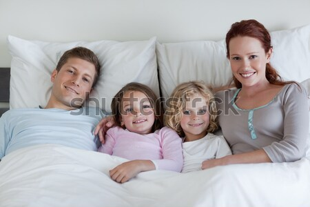 Happy family posing under a duvet while looking at the camera Stock photo © wavebreak_media