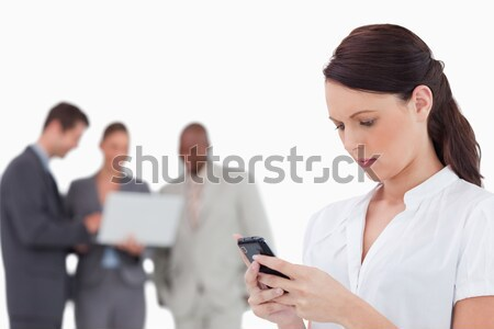 Saleswoman reading text message with colleagues behind her against a white background Stock photo © wavebreak_media