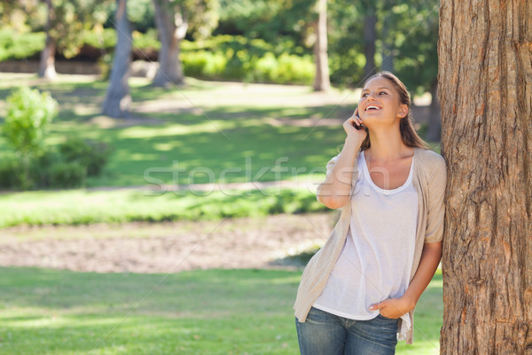 Cheerful woman on the phone leaning against a tree Stock photo © wavebreak_media
