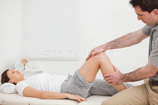 Woman lying while a man manipulating her leg indoors Stock photo © wavebreak_media