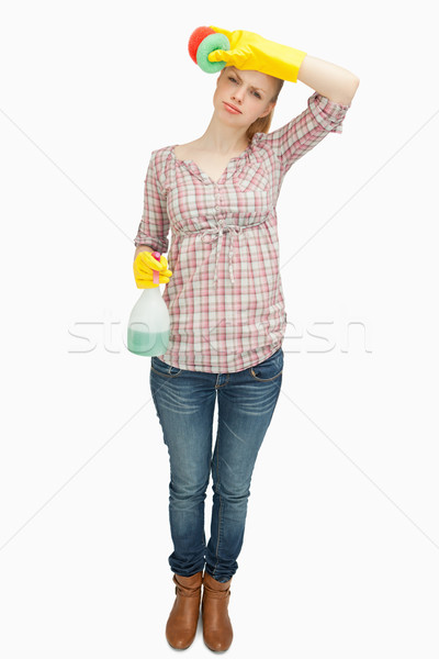 Woman wiping her forehead while holding a spray bottle  against white background Stock photo © wavebreak_media