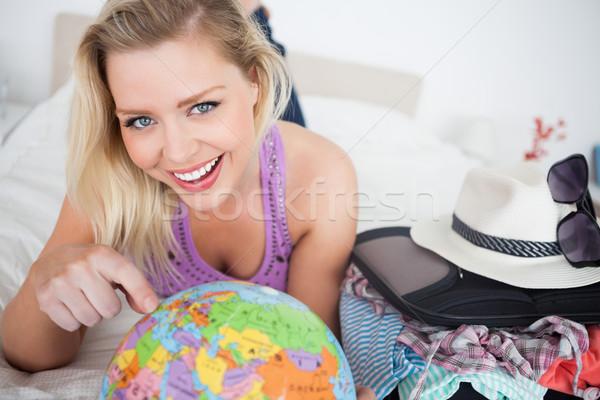 Piękna kobieta walizkę wskazując świecie bed ziemi Zdjęcia stock © wavebreak_media
