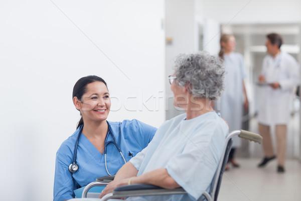Nurse looking at a patient in a wheelchair in hospital ward Stock photo © wavebreak_media