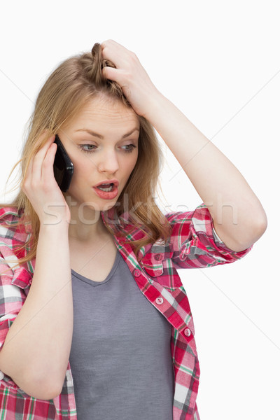 Annoyed woman holding a mobile phone against a white background Stock photo © wavebreak_media