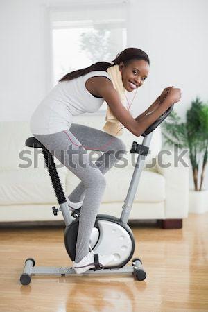 вид сбоку концентрированный черную женщину осуществлять велосипедов гостиной Сток-фото © wavebreak_media