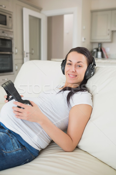 Pregnant woman listening to music with unborn child on sofa in living room Stock photo © wavebreak_media