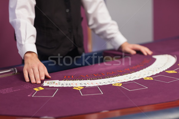 Dealer standing before a table in a casino and dealing out cards Stock photo © wavebreak_media