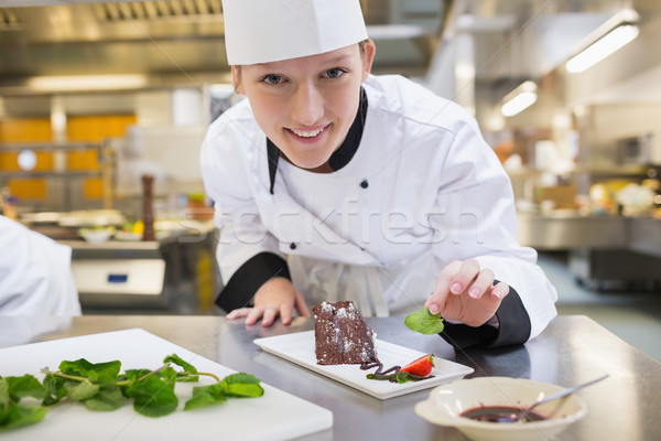 Smiling chef putting mint with her dessert in the kitchen  Stock photo © wavebreak_media