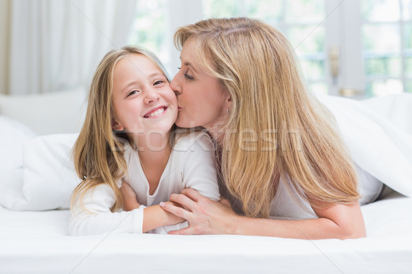 Mother kissing her daughter on the cheek in the bed  Stock photo © wavebreak_media