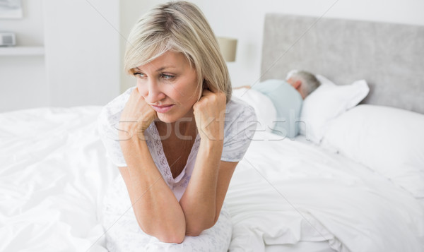Tensed mature woman sitting in bed with man in background Stock photo © wavebreak_media