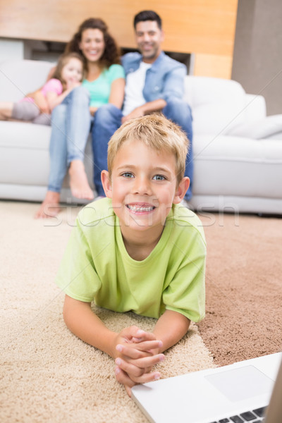 Smiling little boy using laptop on the rug with parents sitting  Stock photo © wavebreak_media