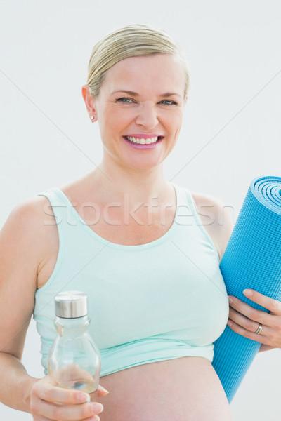 Kobieta w ciąży butelki wody wykonywania uśmiechnięty Zdjęcia stock © wavebreak_media
