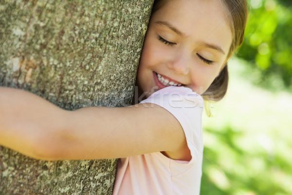 Smiling girl hugging tree with eyes closed at park Stock photo © wavebreak_media