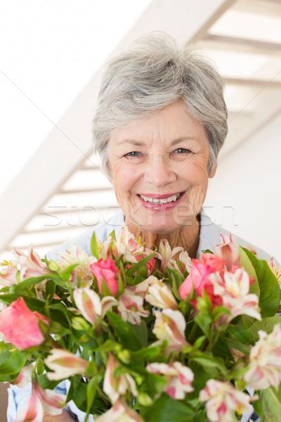 Nyugdíjas nő tart virágcsokor virágok mosolyog Stock fotó © wavebreak_media