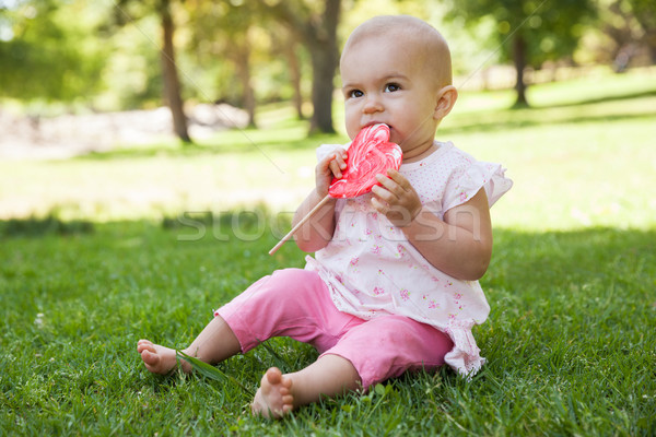 Cute baby with heart shaped lollipop at park Stock photo © wavebreak_media