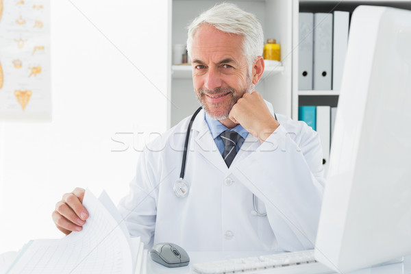 Mature male doctor with computer at medical office Stock photo © wavebreak_media