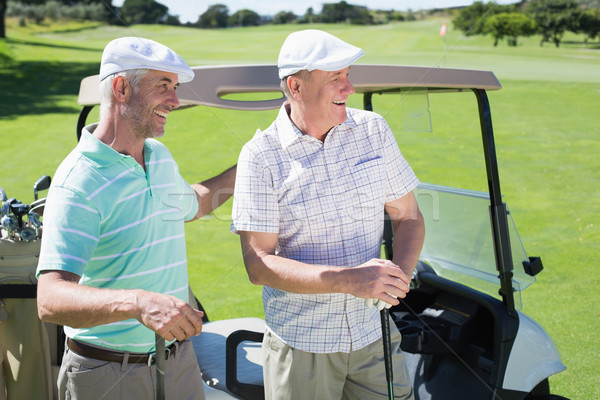 Stock photo: Golfing friends standing beside their buggy smiling