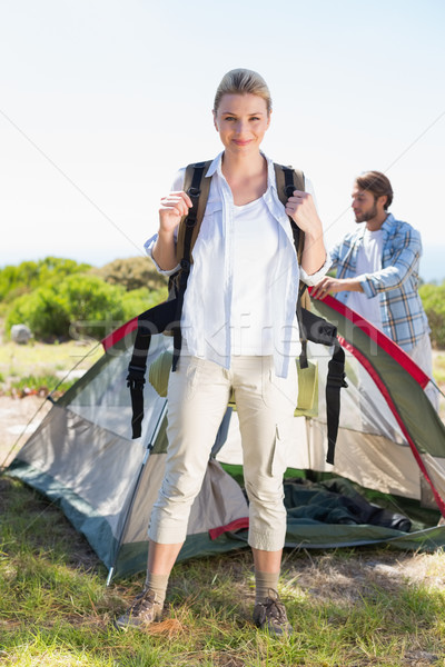 Attractive blonde smiling at camera while partner pitches tent Stock photo © wavebreak_media